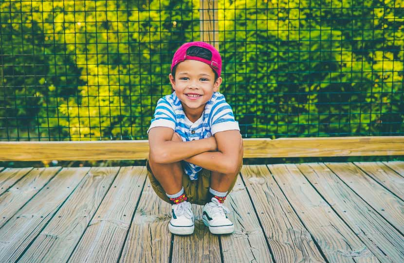 Smiling dark-haired boy wearing a red cap and striped blue shirt crouches on a wooden bridge in front of green trees