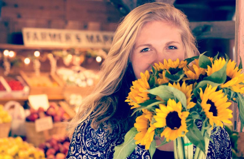 Blonde young woman hides her smile due to a chipped tooth with a bouquet of yellow sunflowers at a farmers market