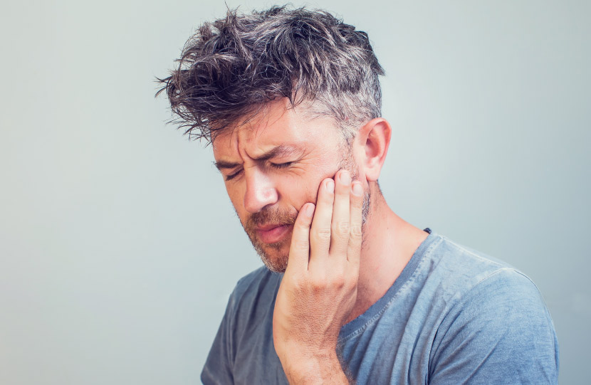 Middle-aged man in a gray shirt touches his jaw in pain because he grinds and clenches his teeth as he sleeps