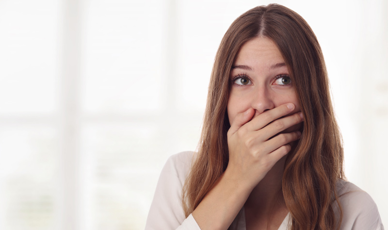 Brunette woman covers her mouth due to bad breath from an untreated cavity