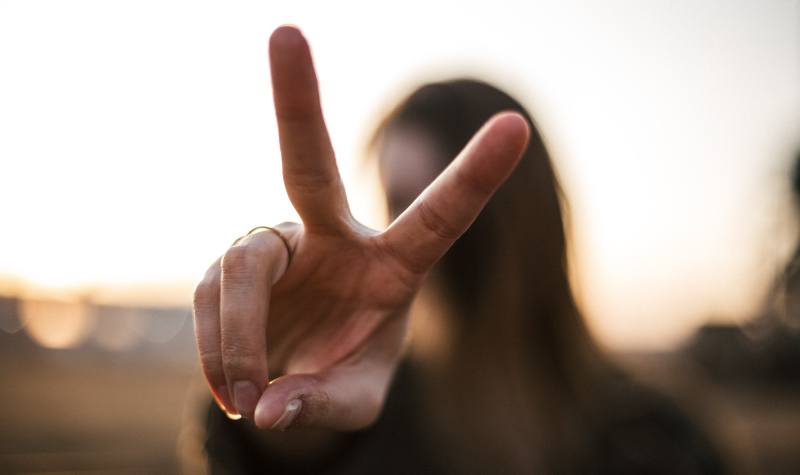 A woman holds two fingers up to represent biannual dental visits