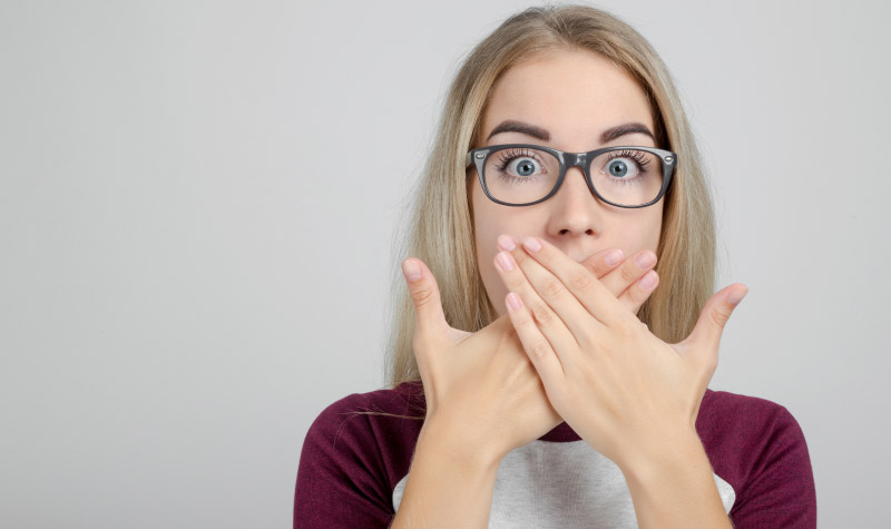 girl with glasses covering her mouth with both hands to hide tooth decay