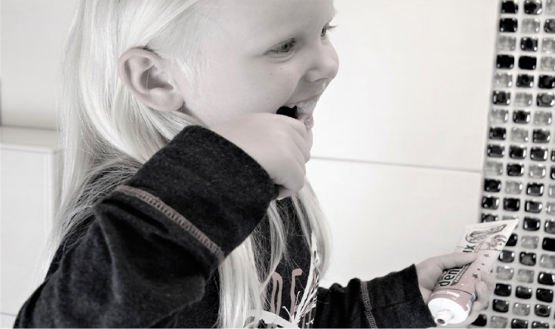 young blond girl brushing her teeth