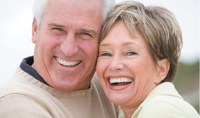 senior couple smiling and laughing after learning how to care for dentures