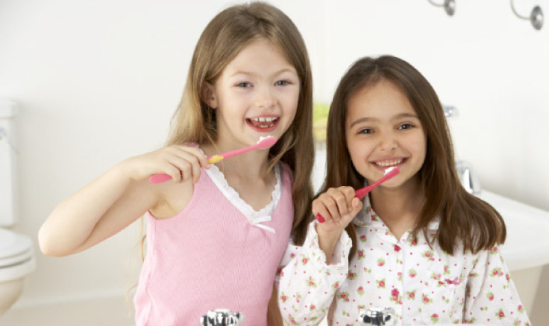 two young girls brushing their teeth together